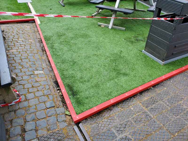 Red GRP nosing used as edging on artificial grass