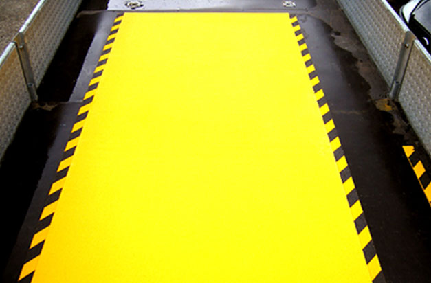 Anti-Slip floor sheets with hazard stripes for a loading area.